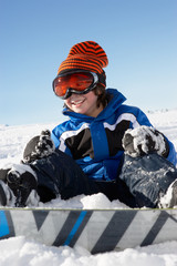 Young Boy Sitting In Snow With Snowboard