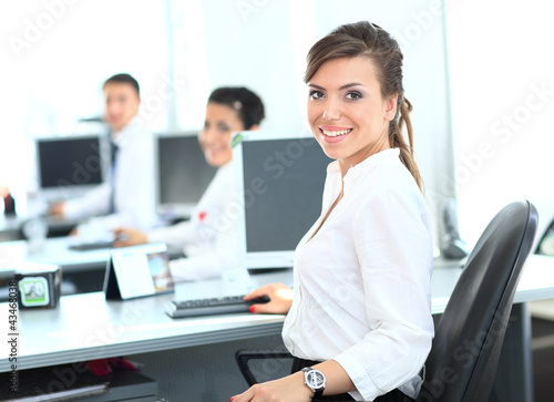 Happy young businesswoman looking behind and