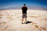 Man looking out over vast salt flat in Death Valley  California poster