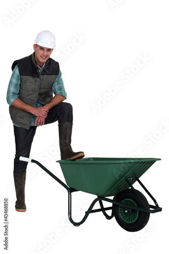 Construction worker with empty wheelbarrow