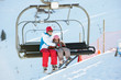 Mother And Daughter Getting Off chair Lift On Ski Holiday In Mou