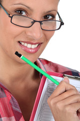 Brunette wearing glasses holding clipboard