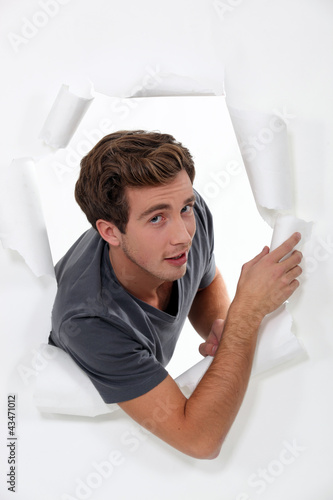 young man looking through hole in torn paper