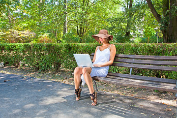 Young elegant woman in park and working on laptop