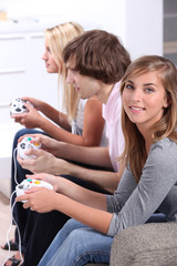 Three teenagers playing video games