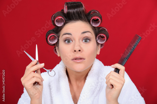 Woman with her hair in curlers holding scissors and a comb