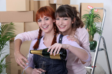 Two female flat-mates celebrating move