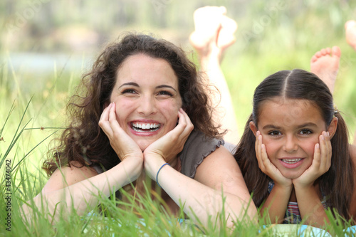 a woman and a little girl lying down in the grass