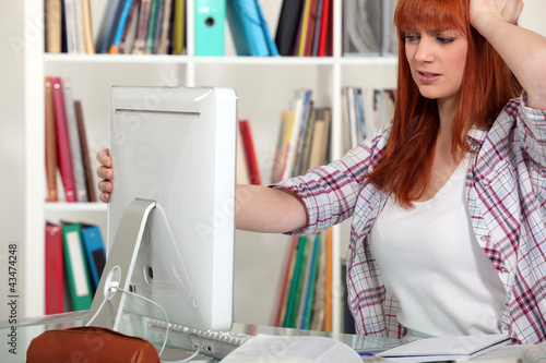 Young woman having trouble with computer