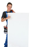Woman with blank board, toolbox and thumbs up
