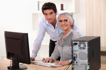 Young man and older woman using a computer