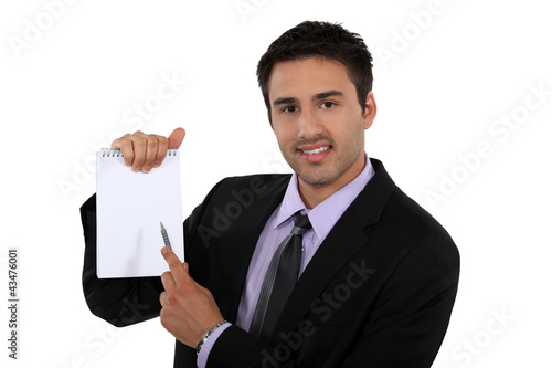Man in suit pointing white notebook