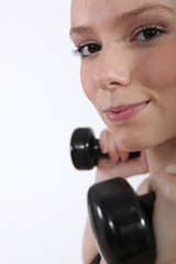 Closeup of a young woman using dumbbells