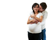 Young pregnant couple hugging on white background