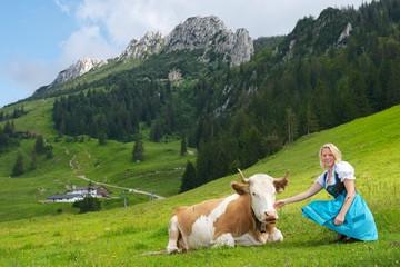 Junge Frau in Tracht mit Kuh vor der Kampenwand