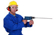 craftsman with protective goggles holding electric drill