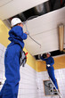 Two electrician repairing ceiling lighting