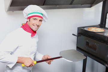 a pizza cook in front of an oven