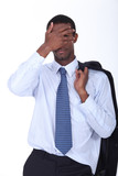 A black businessman hiding his face.