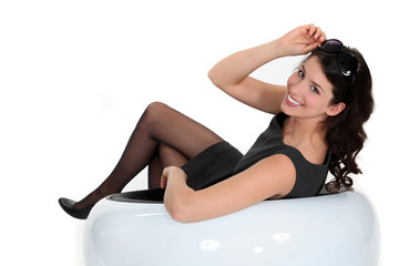 Brunette woman sitting in white chair