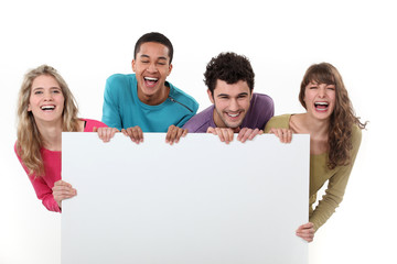 Laughing people holding a board left blank for your message