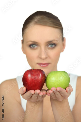 Blurry woman showing apples on white background