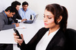 Indian businesswoman using phone with colleagues in ackground