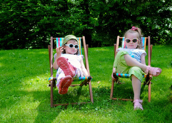 Two little girls are sitting outdoors