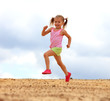 Little girl running in sand