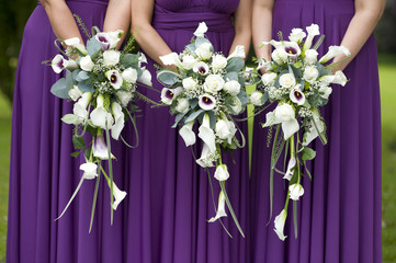 three bridesmaids holding wedding bouquets
