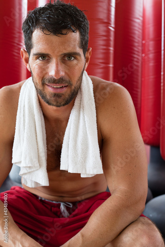 Handsome muscular man smiling in front of red punching bags.