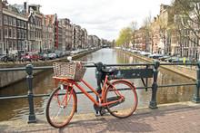 Oranje fiets op de brug in Amsterdam in Nederland