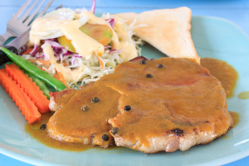 pork steak ready for eat in dish  with blue background