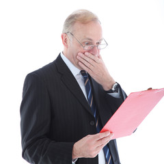 Appalled middle-aged businessman reading a report