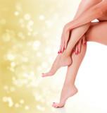 Stunning female legs on golden blurred background.