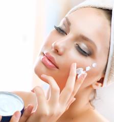 Beautiful Young Woman applying facial moisturizing cream