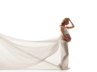 A young blond pregnant woman in white silk clothes