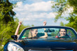 Young couple with cabriolet in summer on day trip