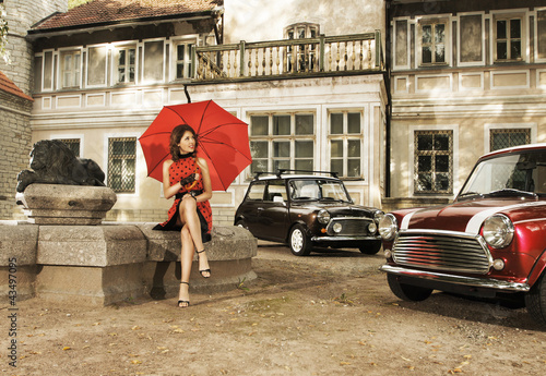 A vintage fashion shoot with a young woman holding an umbrella