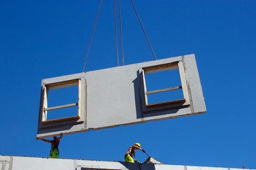 Installing precast concrete wall panel with crane