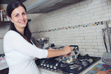 beautiful young brunette woman cooking dinner in the kitchen