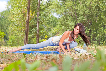 Beautiful young woman doing  yoga exercising  in forest