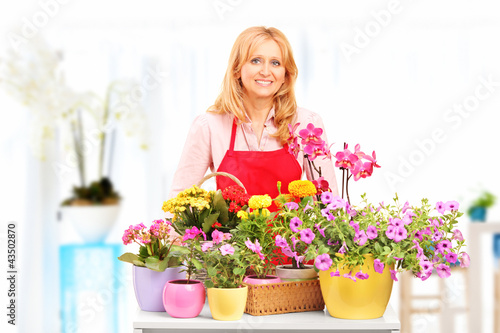 Female horticulturist standing with flowers