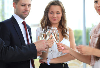 Business people raising toast with champagne at office