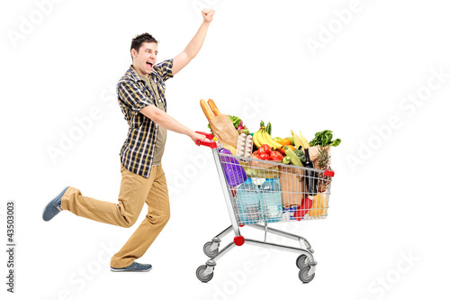 Full length portrait of a happy man pushing a shopping cart