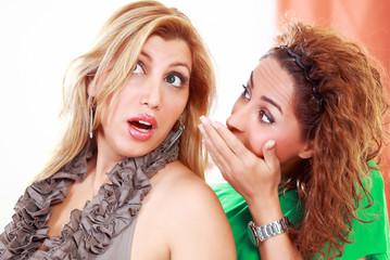 Women gossiping whispering in ear