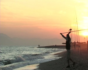 Fisherman throwing at sunset. Surf casting.16 9.