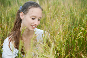 Beautiful woman smiles in wheat field