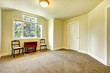 Empty room with yellow walls and brown carpet.