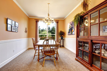 Peach dining room with beige carpet with white border.